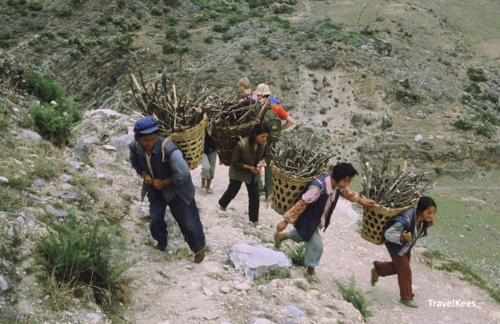 bergbewoners op bergpad met vracht op hun rug