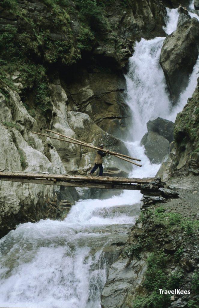 man met boomstammen op zijn schouder steekt een waterval over