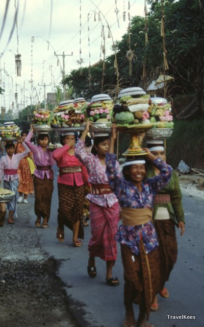 Schalen vol met fruit, rijst, bloemen en wierook in processie door Ubud.