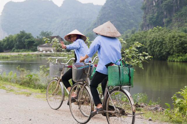 groet van vietnamese vrouw op fiets in ninh binh