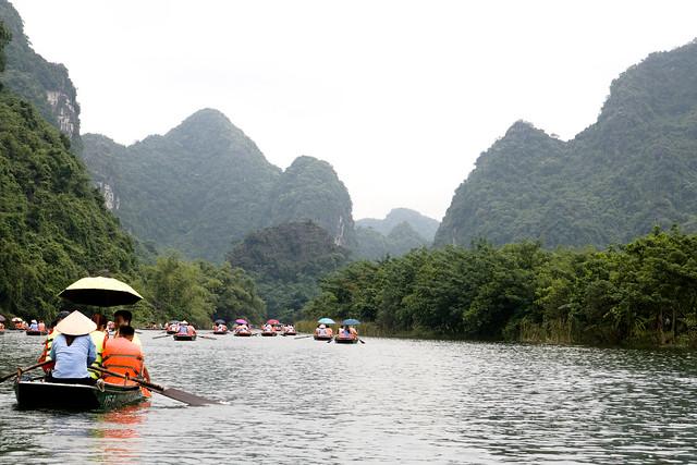 roeibootjes over de rivier bij Trang An met kalksteenbergen