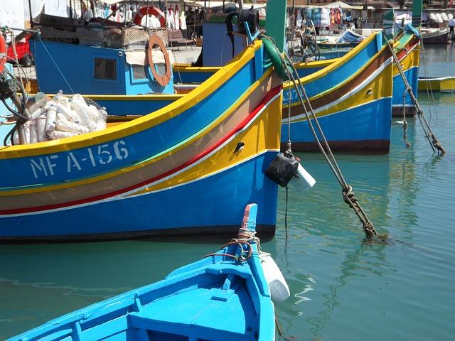 blauw en geel gekleurde bootjes in de haven van Marsaxlokk, Malta