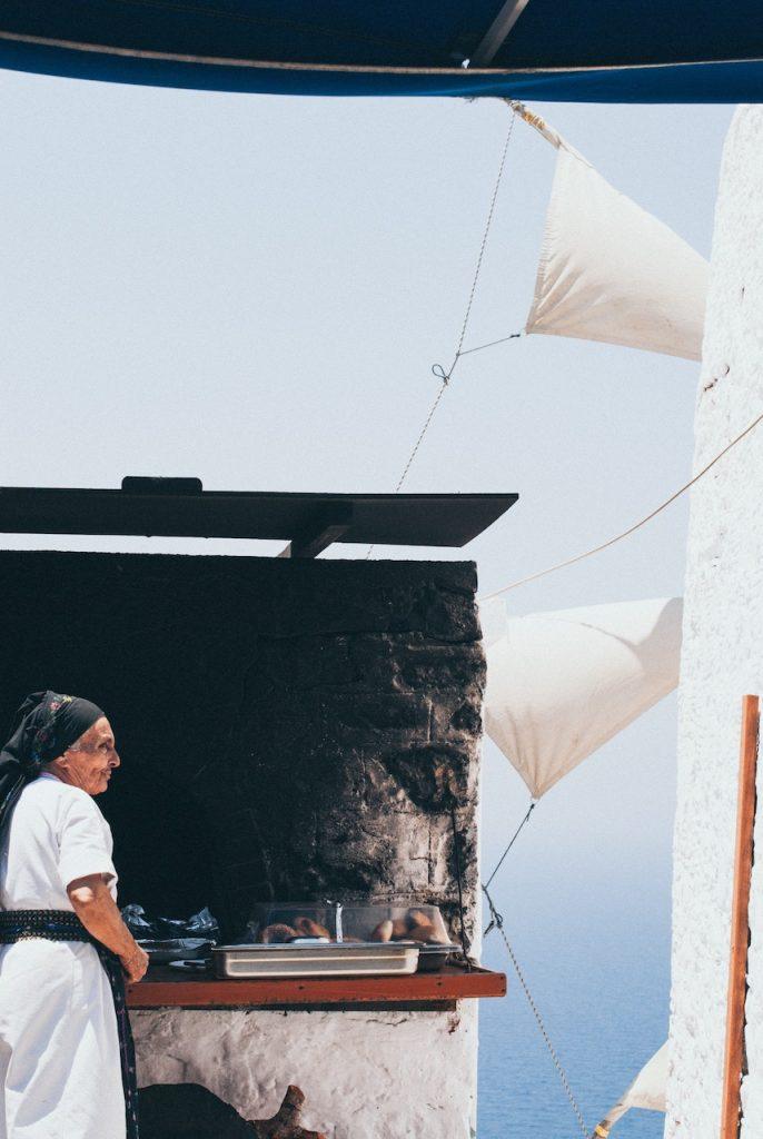 oude vrouw in witte jurk bij Griekse windmolen